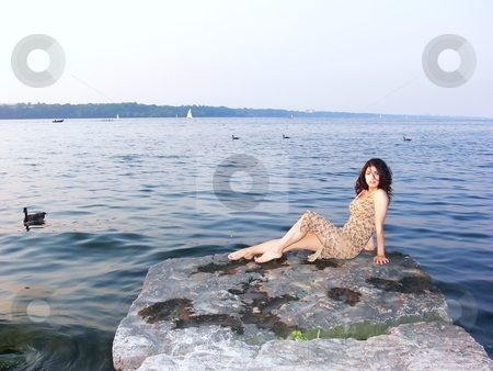 Girl on the lake   stock photo, A young girl sitting on a big rock in the lake Ontario, resting and enjoying the peace and quietness of the water. by Horst Petzold