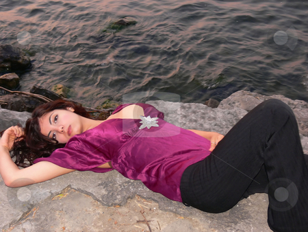 Lady on the lake   stock photo, An lovely young lady laying on a big rock on the lake relaxing by sunset. by Horst Petzold