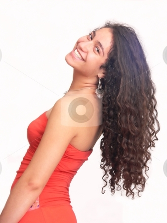 A beautiful girl    stock photo, An pretty young girl in profile turning her head so her nice long curly hair hangs down, in a red dress. On white background. by Horst Petzold
