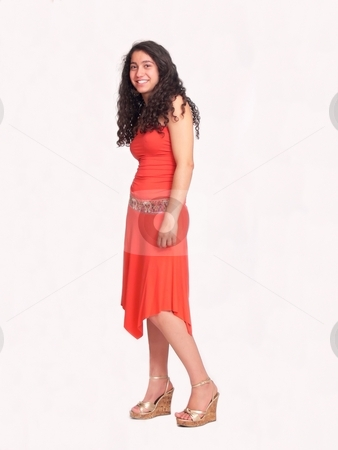 Young girl in red   stock photo, An pretty young girl with long dark hair in an nice red dress is standing and smiling on white background. by Horst Petzold