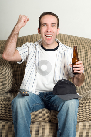 Fist Pumping stock photo, A young man pumping his fist with excitement as he watches tv and enjoys his beer by Richard Nelson