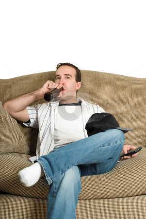 Relaxing stock photo, A young man watching some tv and drinking a bottle of beer, while sitting on a large sofa by Richard Nelson