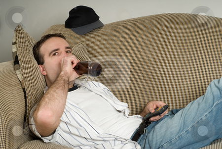 Alcoholic stock photo, A young alcoholic lying on the couch drinking from a bottle of beer while watching tv by Richard Nelson