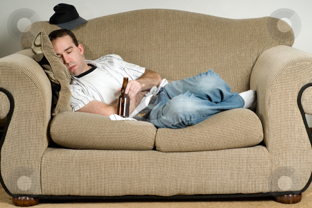 Sleeping With Beer stock photo, A young man sleeping on the couch with a bottle of beer by Richard Nelson