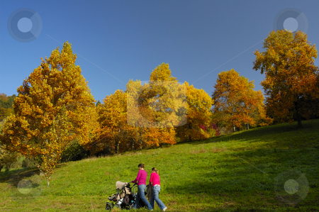 A walk in autumn stock photo, Two young mothers walk with their pushchairs past trees bright with autumn colours. by Alistair Scott