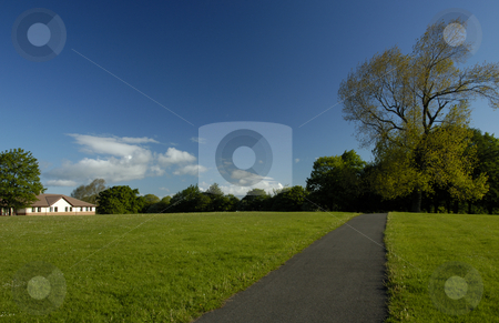 Path stock photo, A path stretching away across an empty park with an almost clear blue sky in the background. Space for text in the sky or on the grass. by Alistair Scott