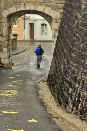 Urban walker stock photo, A hiker walks under the arch in the Swiss village of Aubonne on a wet day. Slight motion blur on his feet and backpack straps. by Alistair Scott