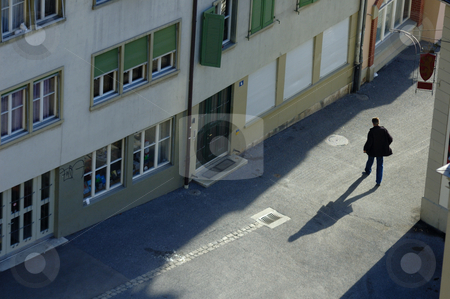 Shadow man stock photo, A man walks through the streets of the Swiss federal capital, bern, in the early morning. by Alistair Scott