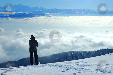 Looking across the valley stock photo, A skier, high on a slope in the Swiss Jura mountains in winter, takes a break from skiing and gazes across to the French Alps. The valley below is filled with cloud, what the Swiss call the 'Mer de Brouillard' (sea of mist). by Alistair Scott