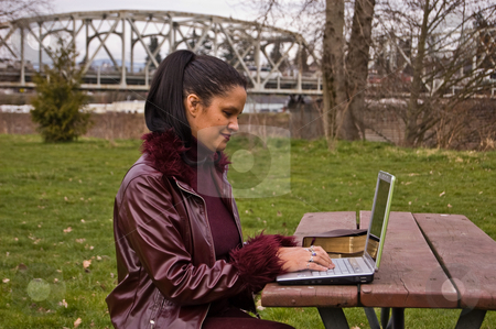 Young Professional Woman at Park Working on Laptop stock photo, Young multi racial (Jamaican, Irish & Native American) woman in late 20's, is at work on her laptop on a picnic table at an outdoor park. by Valerie Garner