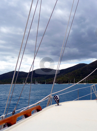 Sailing in blue waters among tropical islands stock photo, View across the deck of a sailboat on a cloudy day by Jill Reid