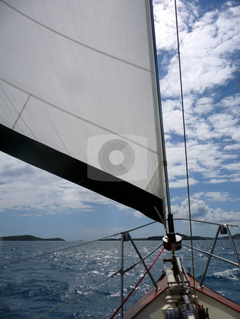 Wind in the mainsail on a cloudy day stock photo, View across the deck and the mainsail of a sailboat on a cloudy day by Jill Reid