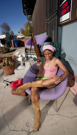 Black woman on back patio with rifle stock photo, Black woman with rifle in front of house with messy yard by Scott Griessel