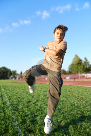 Boy in Action stock photo, Teenage boy jumping in a green grass covered sports field on a sunny day. by Denis Radovanovic