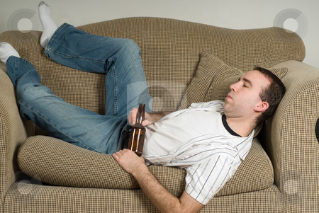 Drinking Problem stock photo, A man with a drinking problem is relaxing on a sofa by Richard Nelson