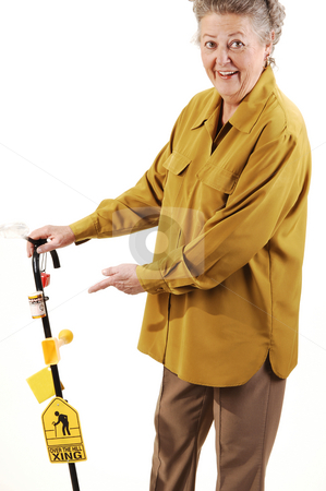 Senior woman with cane. stock photo, Senior woman with gray hair and an dark yellow jacket needs the help of a cane to get around. On white background. by Horst Petzold