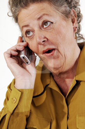 Senior woman on the cell phone. stock photo, A senior woman in an dark yellow jacket talking on the cell phone. On white background. by Horst Petzold