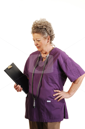 Senior nurse. stock photo, An elderly nurse in a lilac top with the stethoscope around her neck and the clip board in her hand. On white background. by Horst Petzold