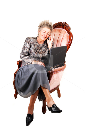 Business woman in armchair. stock photo, Busy businesswoman talking on the cell phone and working also on the laptop, sitting in a pink armchair, over white background. by Horst Petzold