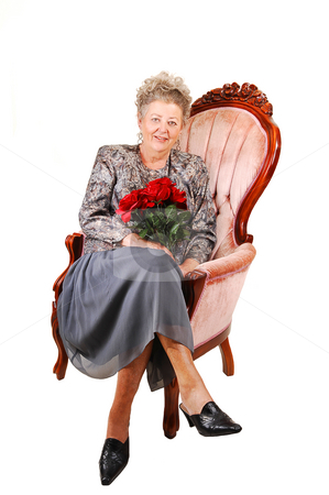 60th birdsday for grandma. stock photo, All dressed up elderly woman with red roses in her hand, for her 60th birdsday. Sitting in a pink armchair for white background. by Horst Petzold