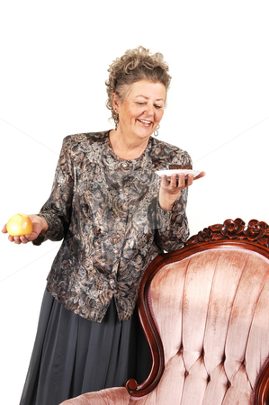 60th birdsday for grandma. stock photo, An elderly woman has to make a choise between an healthy apple on a sweet and delicious piece of shocolate cake. Over white background. by Horst Petzold