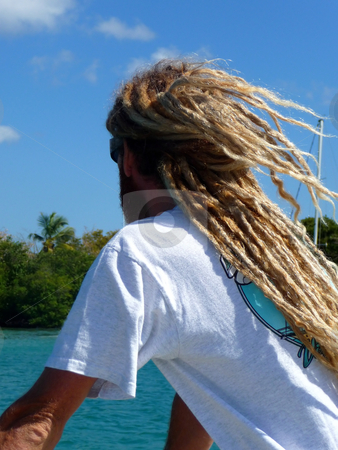 Man with rasta hairstyle looking at ocean stock photo, Adult man with rasta hairstyle relaxing and looking at the ocean by Jill Reid