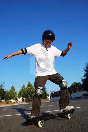 Fun on Skateboard stock photo, Teenage boy having fun skateboarding on a parking lot on a sunny day. by Denis Radovanovic