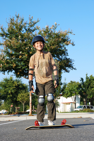 Having Fun With Skateboard stock photo, Teenage boy smiling with a skateboard on the ground on a sunny day with blue sky and trees in the background. by Denis Radovanovic