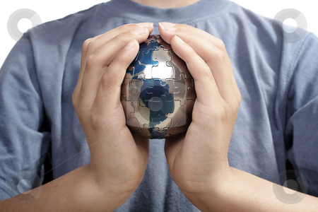 The Missing Piece stock photo, Earth puzzle, held by a young boy looking for solution by Christopher Meder