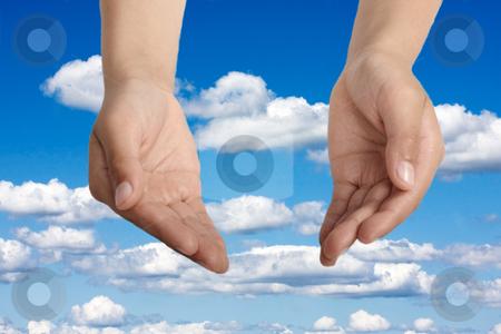 Hands open in religious prayer  stock photo, Hands open in religious prayer against sky background by Christopher Meder