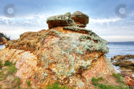 Beachside Boulder stock photo, Beachside boulder against blue sky and green grass by Christopher Meder