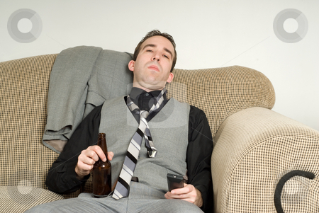 Bored Businessman stock photo, A bored businessman sitting on his sofa at home and holding a beer by Richard Nelson