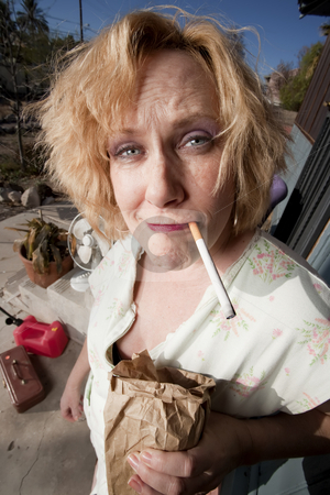Smoking woman on her porch stock photo, Woman with and beer cigarette on her front porch by Scott Griessel