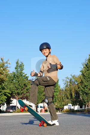 Skateboarding Fun stock photo, Smiling teenage boy with his thumbs up standing on a skateboard on a sunny day with blue sky and trees in the background. by Denis Radovanovic