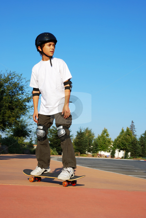 Teen Boy on Skateboard stock photo, Teenage boy riding a skateboard on the sidewalk of a parking lot on a sunny day with blue sky and trees in the background. by Denis Radovanovic
