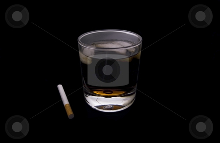 Drink and a smoke stock photo, Drink and a smoke on a black background by John Teeter
