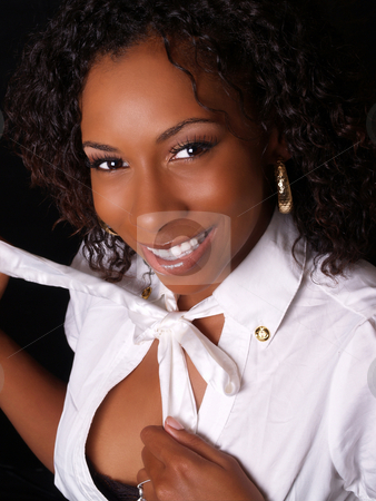 Pretty smiling black woman starting to undress stock photo, Young black woman smiling while starting to remove blouse by Jeff Cleveland
