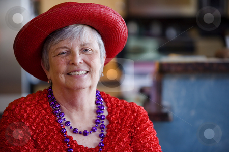 Senior Woman Wearing Red Hat stock photo, Friendly senior woman wearing a red hat by Scott Griessel