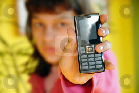 Teen girl showing her mobile phone stock photo, Teen girl showing her mobile phone over yellow by Julija Sapic