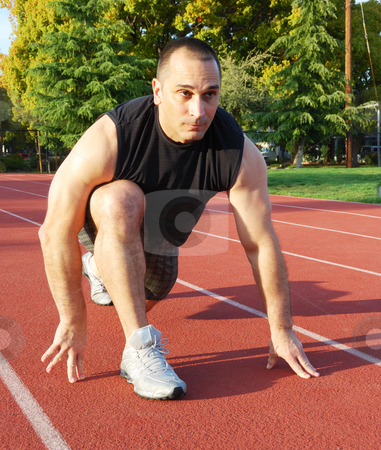 Ready To Run stock photo, Male athlete getting ready to run on an athletic track with trees in the background on a sunny day. by Denis Radovanovic