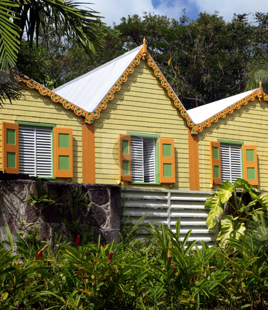 Brightly colored caribbean buildings stock photo, Lush green foliage aroiund brightly colored buildings on a tropical island by Jill Reid