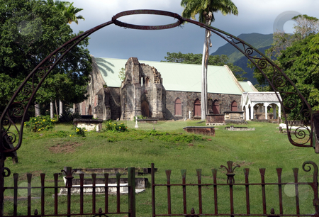 Stone church and cemetery framed by iron gate in St. Kitts stock photo, Old stone church and cemetery framed by iron gate and steel halo by Jill Reid