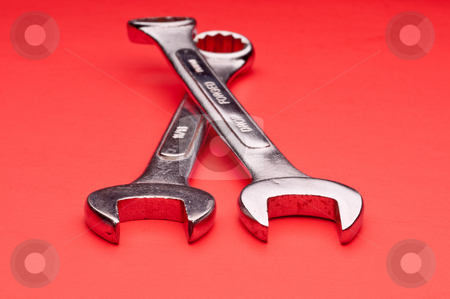Horizontal image of a pair of old worn combination wrenches on a stock photo, Horizontal image of a pair of old worn combination wrenches on a red background by Vince Clements