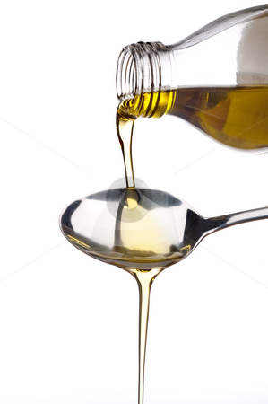Olive oil being poured onto a spoon stock photo, Pure virgin olive oil being poured out of a glass bottle onto a spoon by Vince Clements