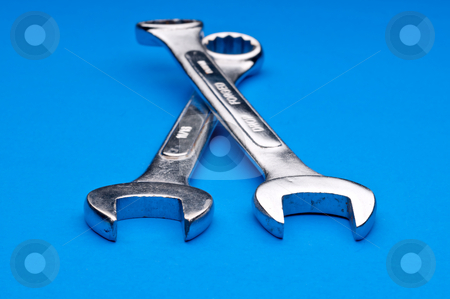 Horizontal image of a pair of old worn combination wrenches on a stock photo, Horizontal image of a pair of old worn combination wrenches on a blue background by Vince Clements