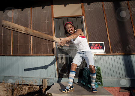Woman swinging a board stock photo, African American woman swinging a board on her front porch by Scott Griessel