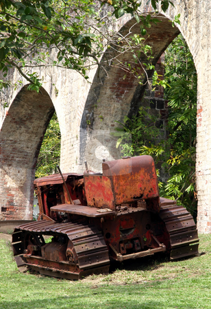 Antique rusted farming tractor and arched stone walls stock photo, An old antique rusted farming tractor by a arched stone structure by Jill Reid