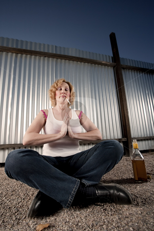 Smoking and drinking woman meditating stock photo, Woman meditating with cigarette and tequila bottle by Scott Griessel