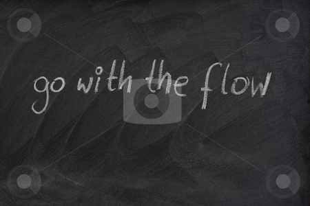 Go with the flow phrase on blackboard stock photo, Go with the flow phrase handwritten with white chalk on blackboard with erase smudge patterns by Marek Uliasz