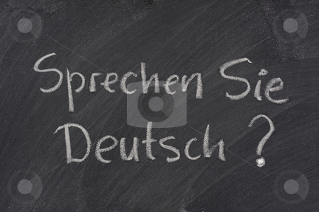Do you speak German question on a blackboard stock photo, Sprechen Sie Deutsch? Do you speak German question handwritten with white chalk on a blackboard with eraser smudges by Marek Uliasz